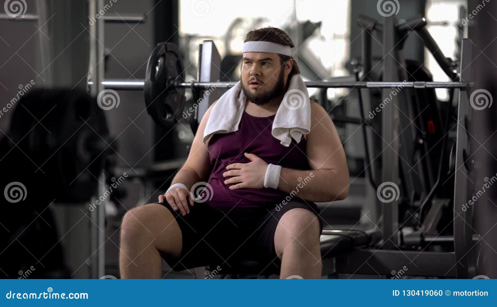 Pancia di segno maschio di peso eccessivo divertente, esaurita dopo l allenamento, insicurezze