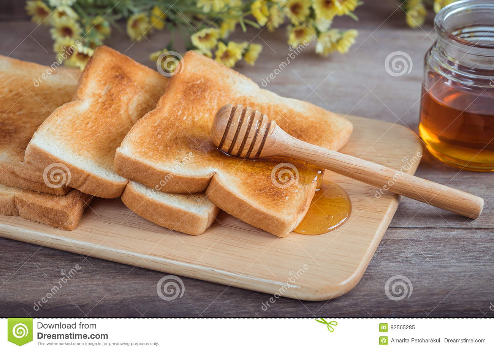 Pane tostato con miele sul piatto di legno