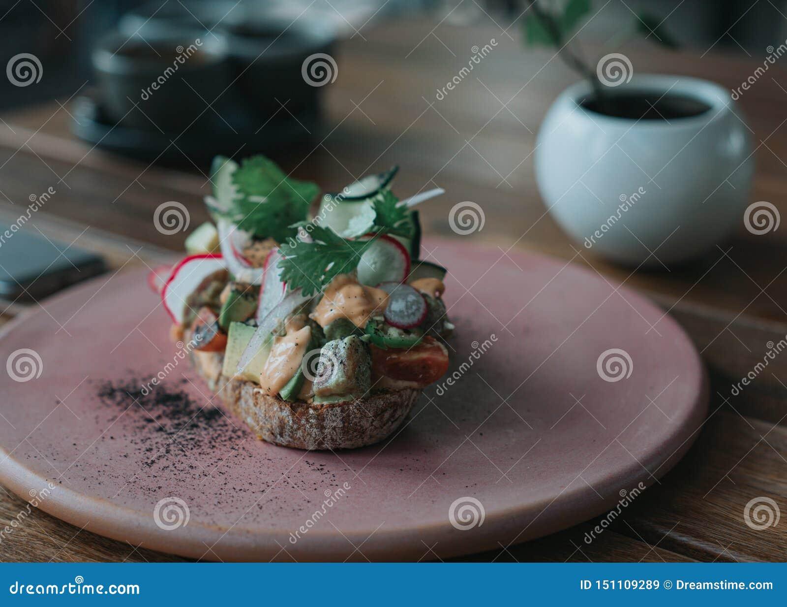 Pane tostato delizioso dell avocado con pane artigianale su un piatto rosa