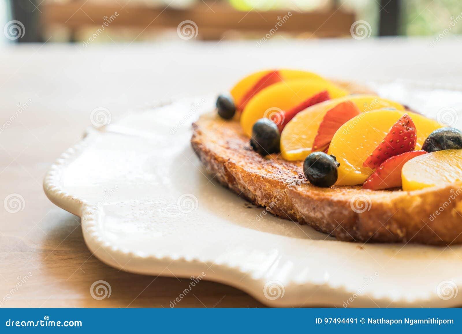 Pane tostato francese con la pesca, la fragola ed i mirtilli