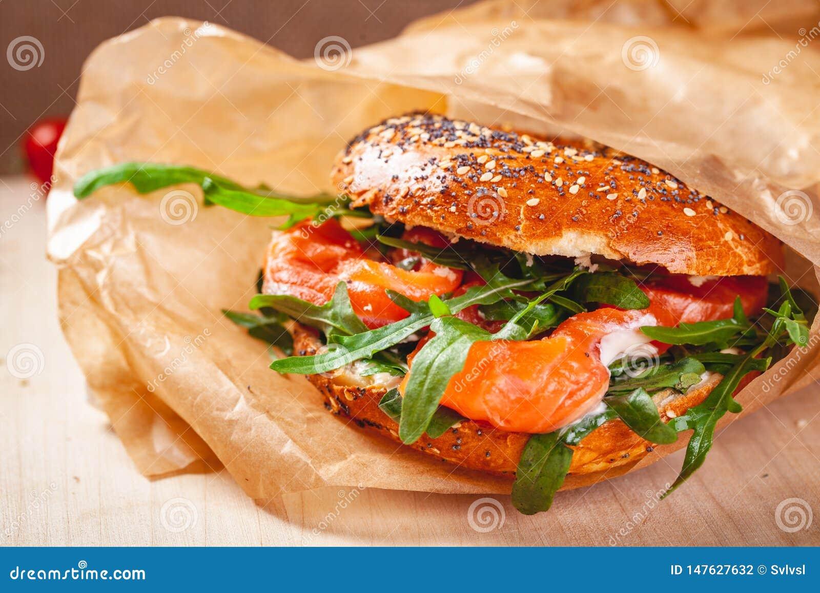 Panecillo con la ensalada del queso cremoso, del salm?n ahumado y del arugula en bolsa de papel marr?n