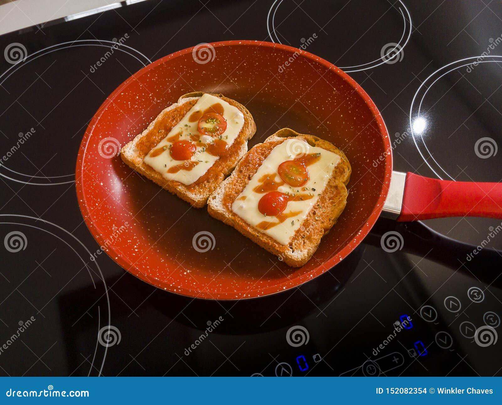 Panes en el sartén rojo en la inducción Cooktop