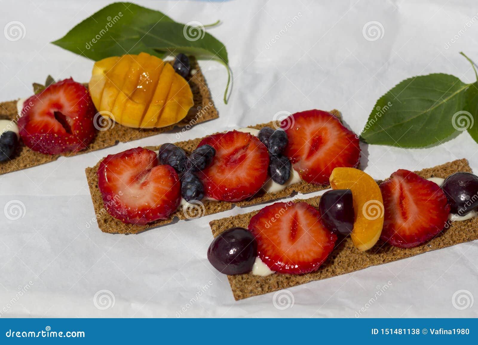 Pani tostati sani e saporiti con la ricotta, i frutti e le bacche su una carta pergamena bianca