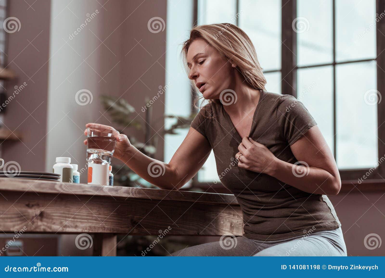 Blonde woman suffering from panic attacks taking pills