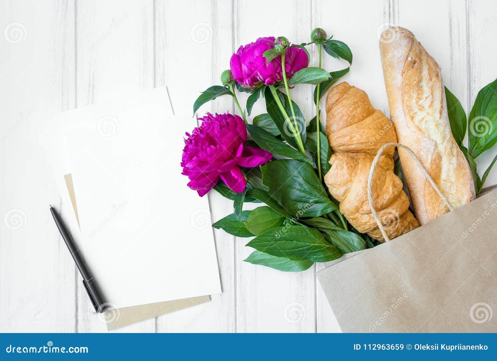Panier de papel con el pan fresco, los cruasanes, las flores y la endecha del plano de la lista de compras, visión superior de la