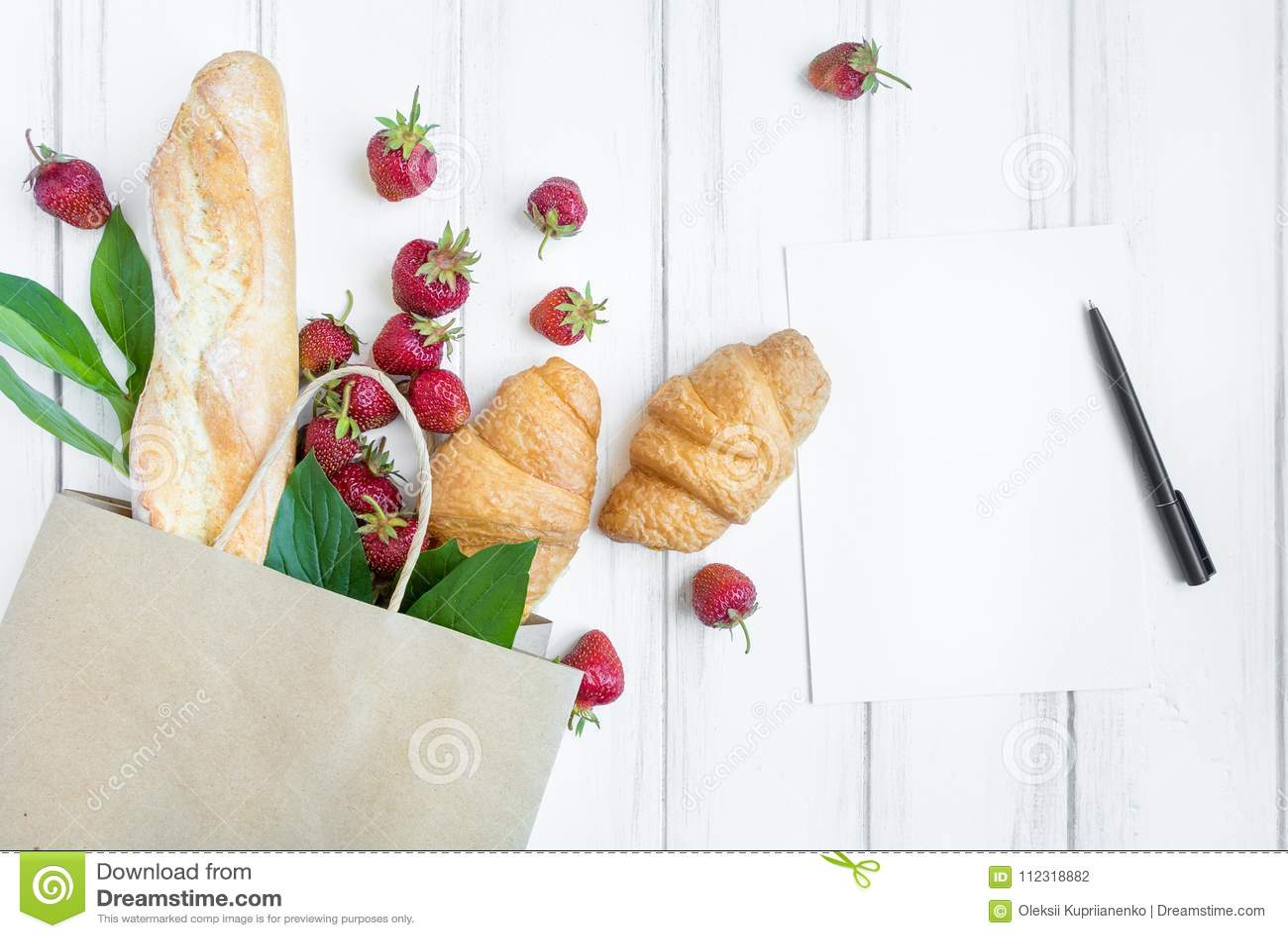 Panier de papel con pan fresco, cruasanes, las fresas y la endecha del plano de la lista de compras, visión superior