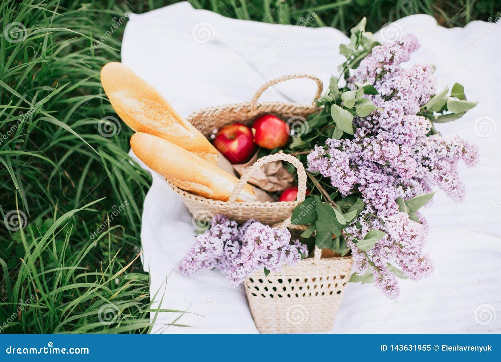 Panier de pique-nique avec des boissons, des fruits et des fleurs sur l herbe verte en dehors au printemps du parc