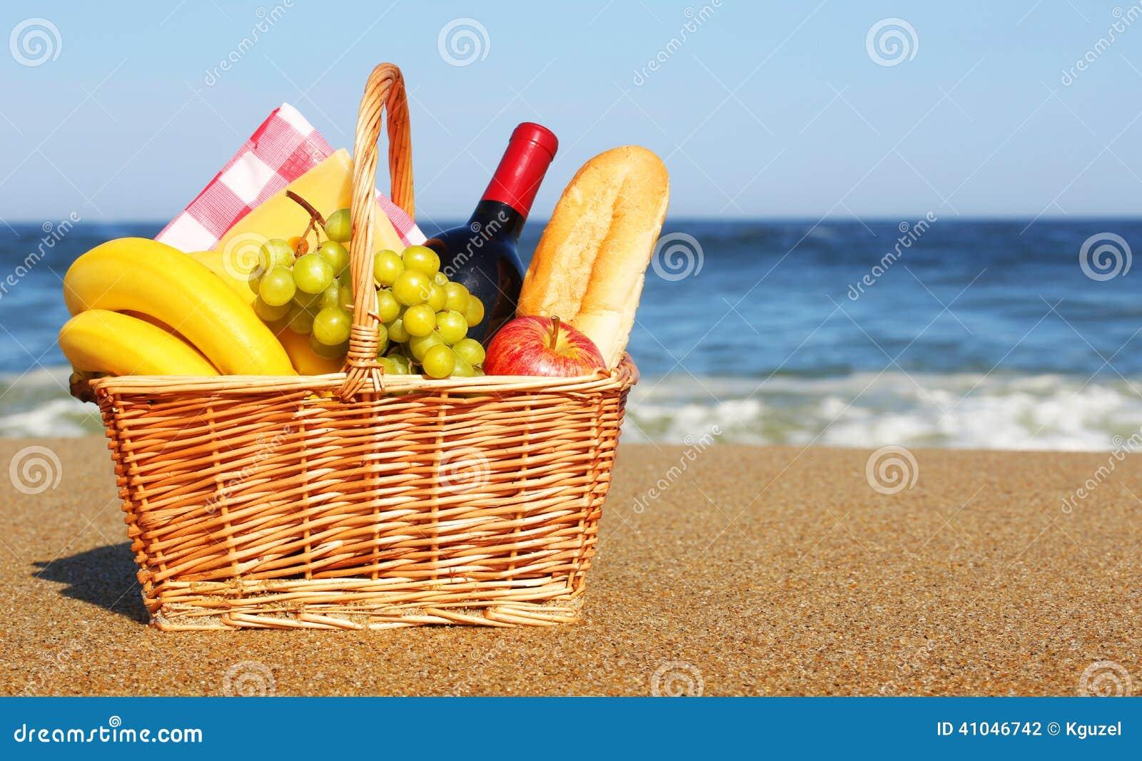 panier de pique nique avec la nourriture sur la plage. Black Bedroom Furniture Sets. Home Design Ideas
