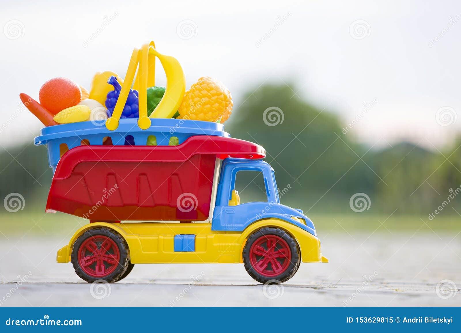 Panier de transport de jouet de camion coloré en plastique lumineux de voiture avec des fruits et légumes de jouet dehors le jour