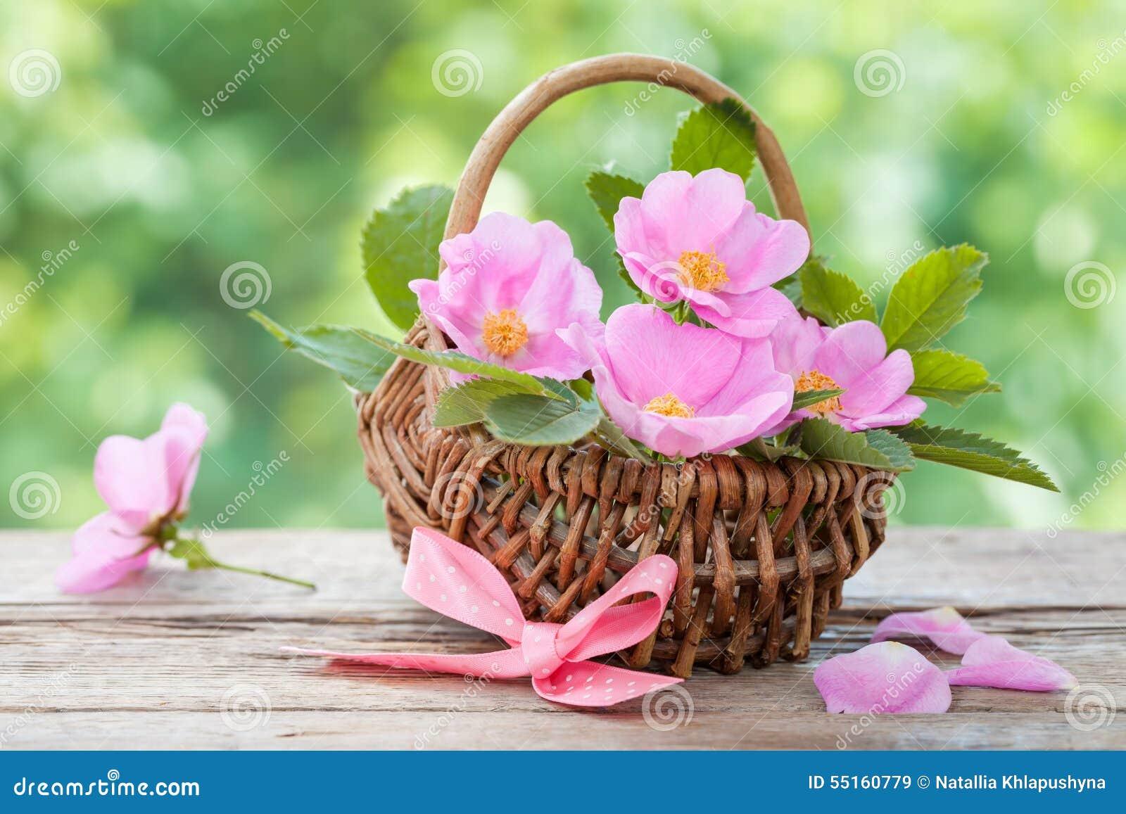 panier en osier avec les fleurs roses sauvages décorums de mariage