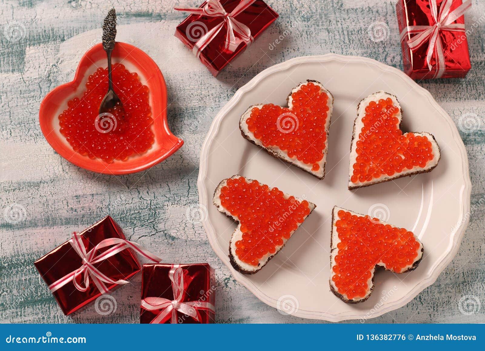Panini con il formaggio cremoso rosso e del caviale sotto forma di un cuore per il San Valentino
