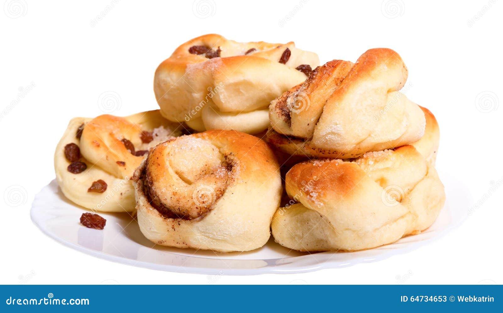 Panini rubicondi dorati con l uva passa su un piatto bianco