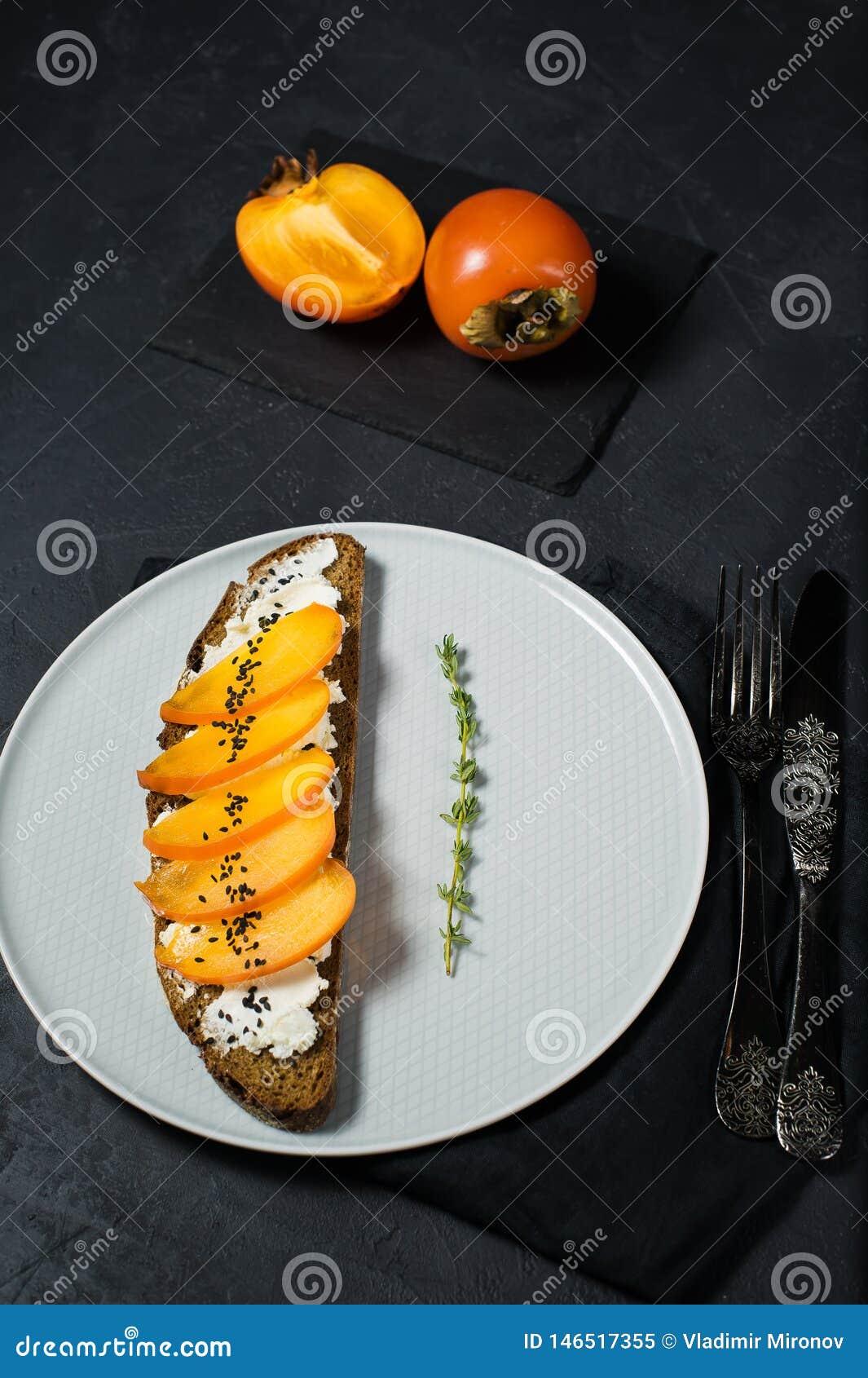 Panino con il cachi e formaggio a pasta molle su un fondo nero