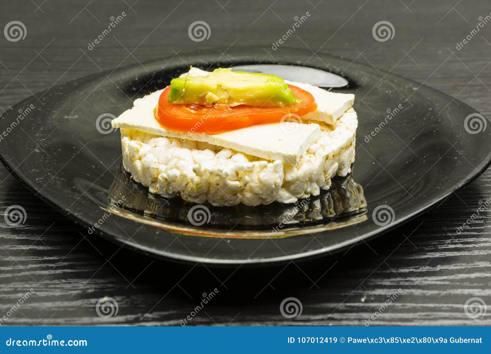 Panino del dolce di riso con formaggio, il pomodoro e l avocado
