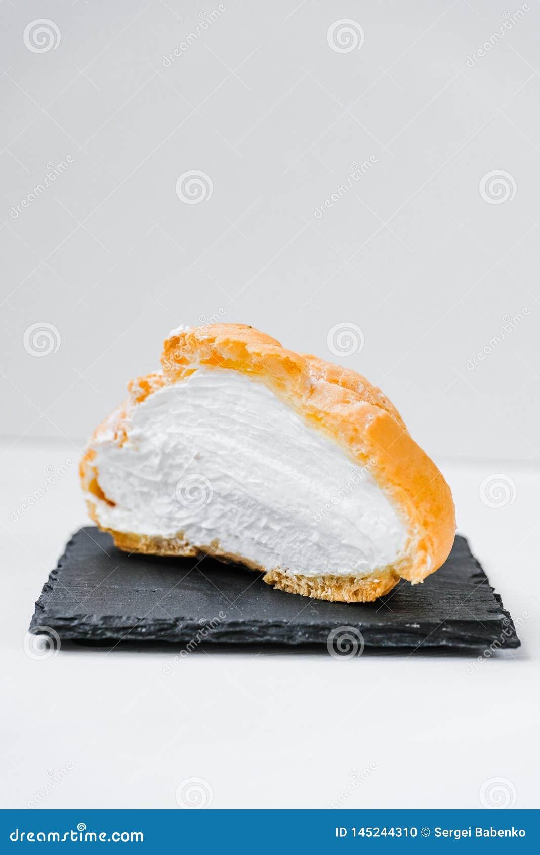 Panino dolce in un taglio con inceppamento e crema sui piatti di uno scisto e sul fondo di legno