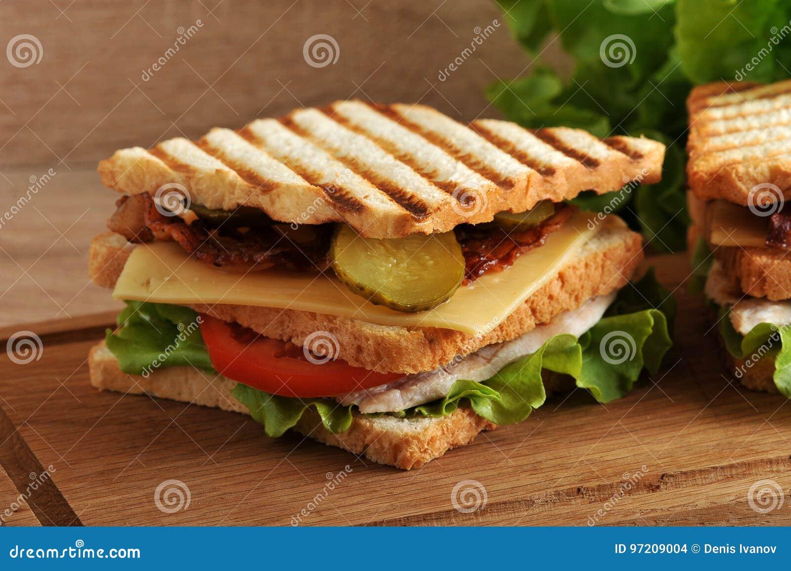 Panino a più strati con formaggio, il prosciutto, i pomodori, i sottaceti ed il le
