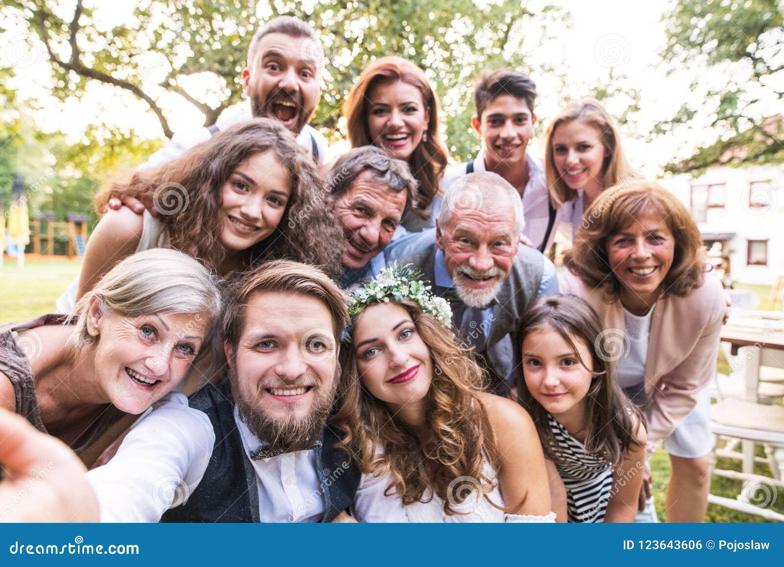 Panna młoda, fornal z gościami bierze selfie przy weselem outside w podwórku
