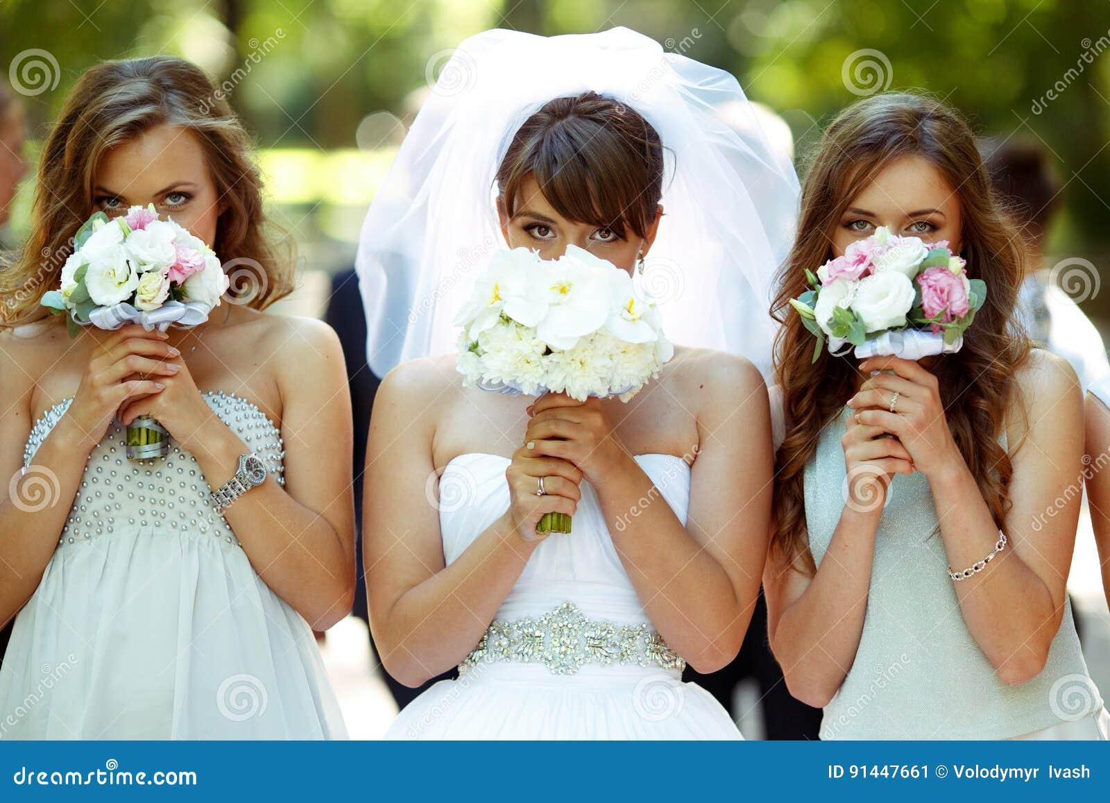 Panna młoda i drużki chujemy ich twarze za małym ślubnym bou