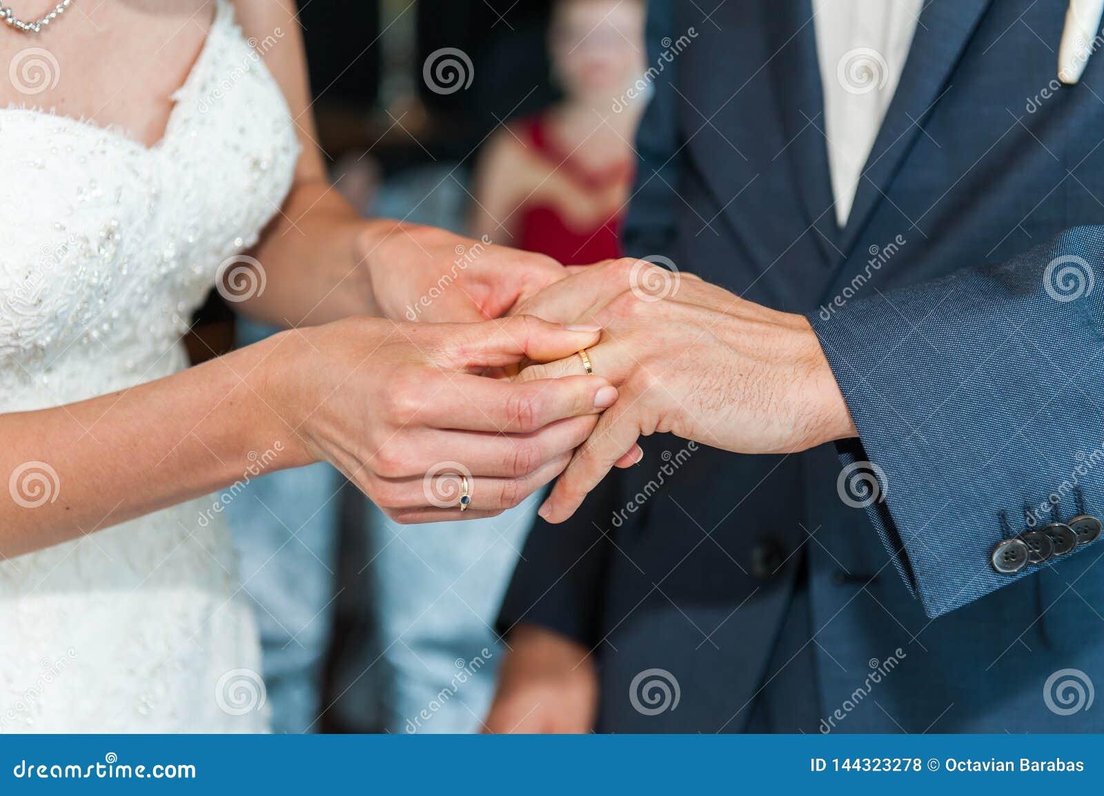 Panna młoda stawiająca na obrączce ślubnej na fornalach dotyka