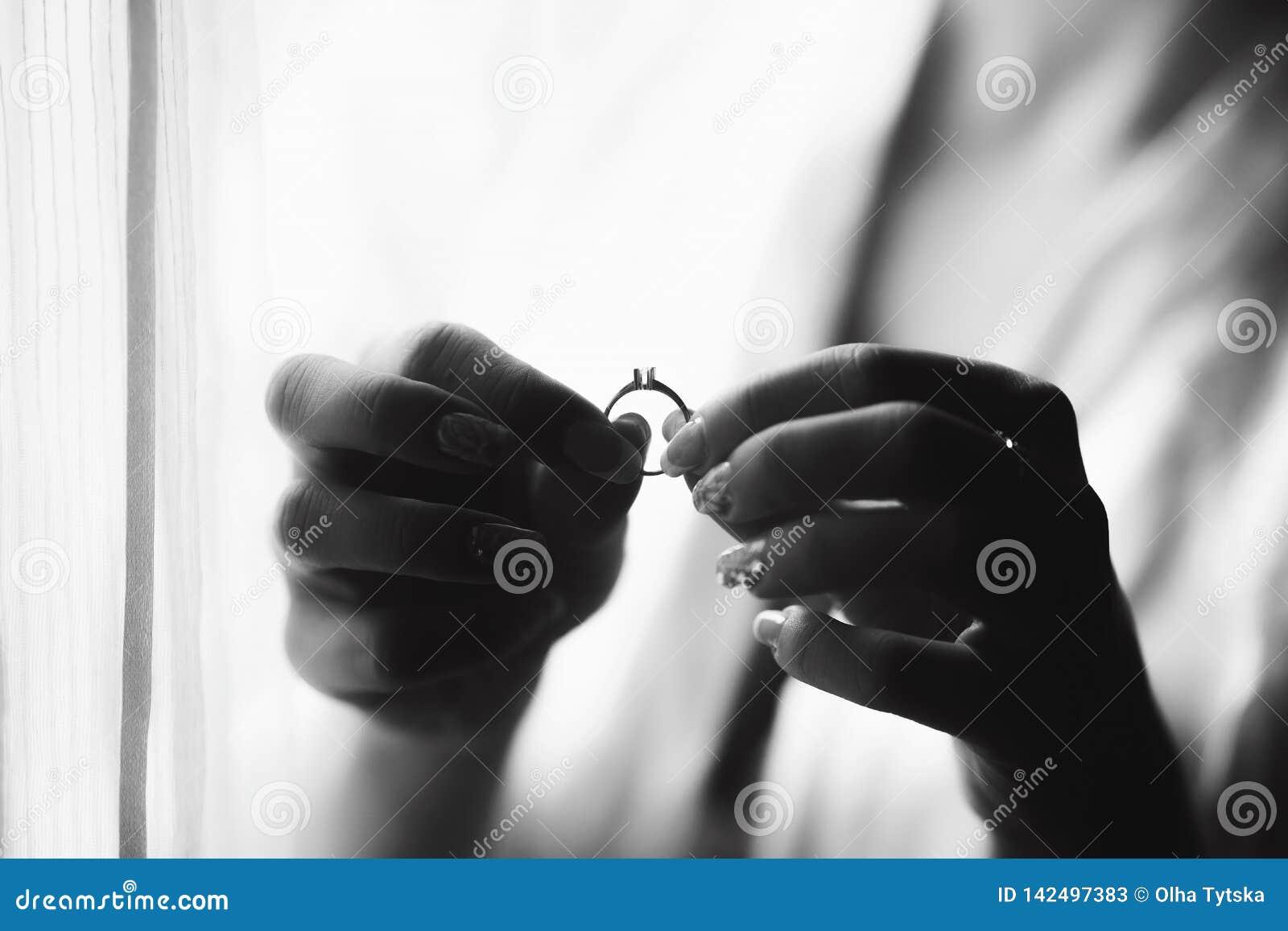 Panna młoda trzyma pierścionek w rękach blisko okno