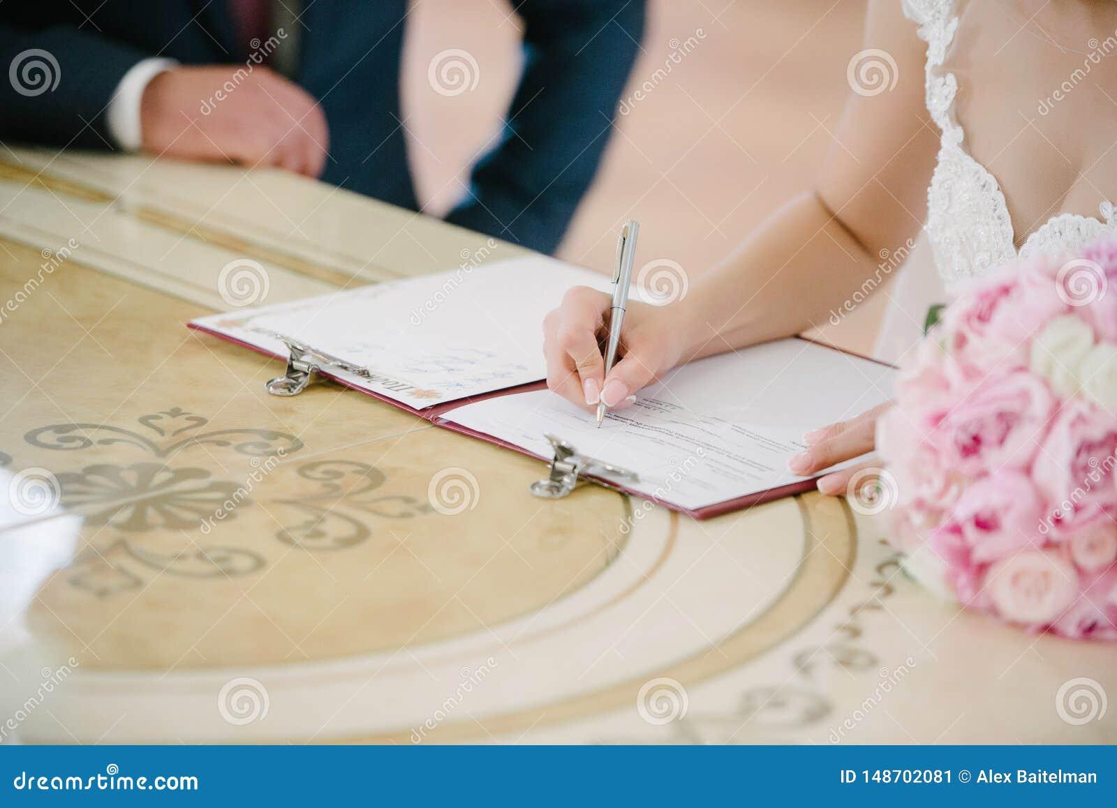 Panna m?oda podpisuje na rejestracji w dokumencie na dzie? ?lubu