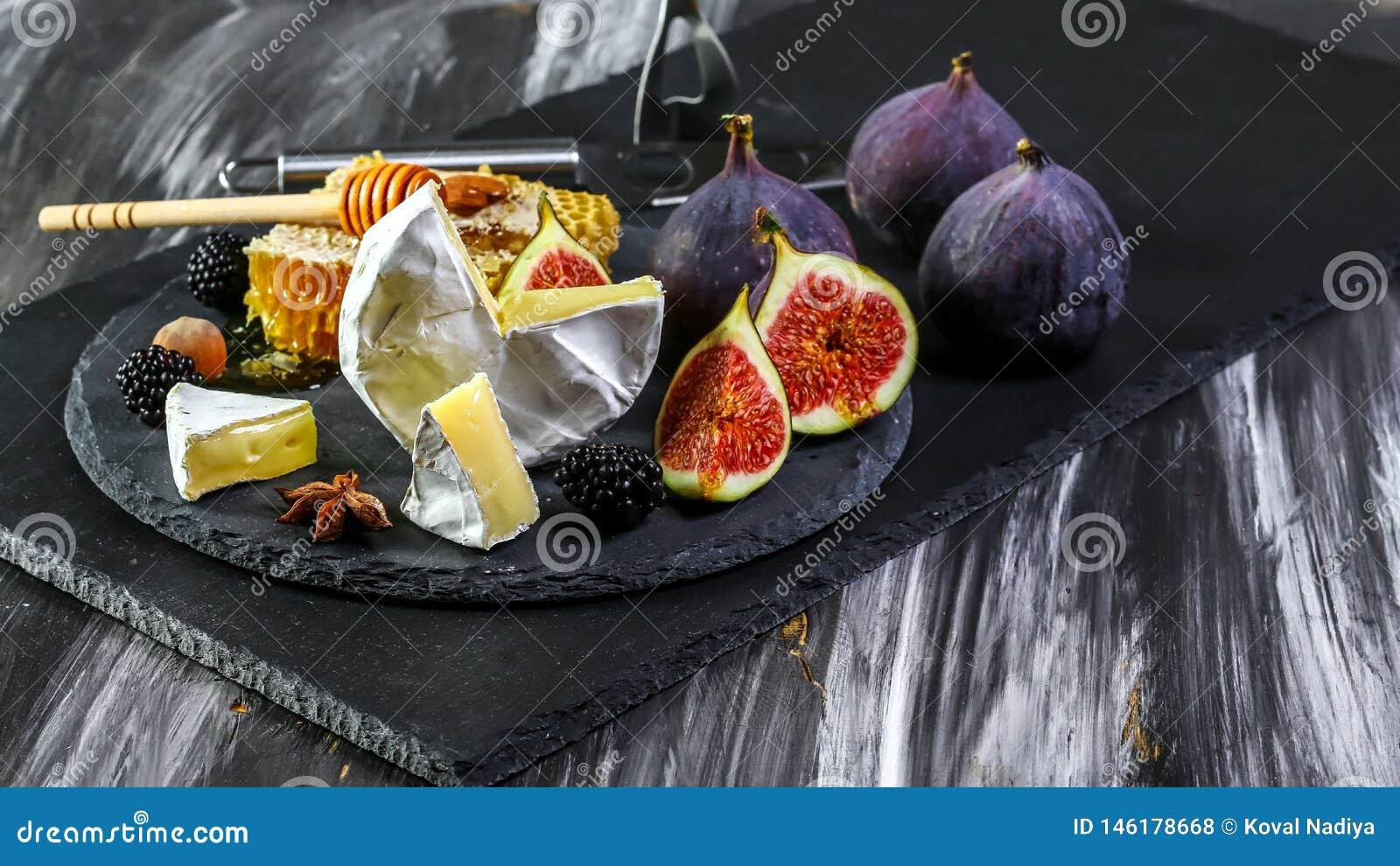 Panneau de fromage, camembert avec des figues et miel Panneau de fromage, camembert avec les figues et le vin de miel et blanc Fo