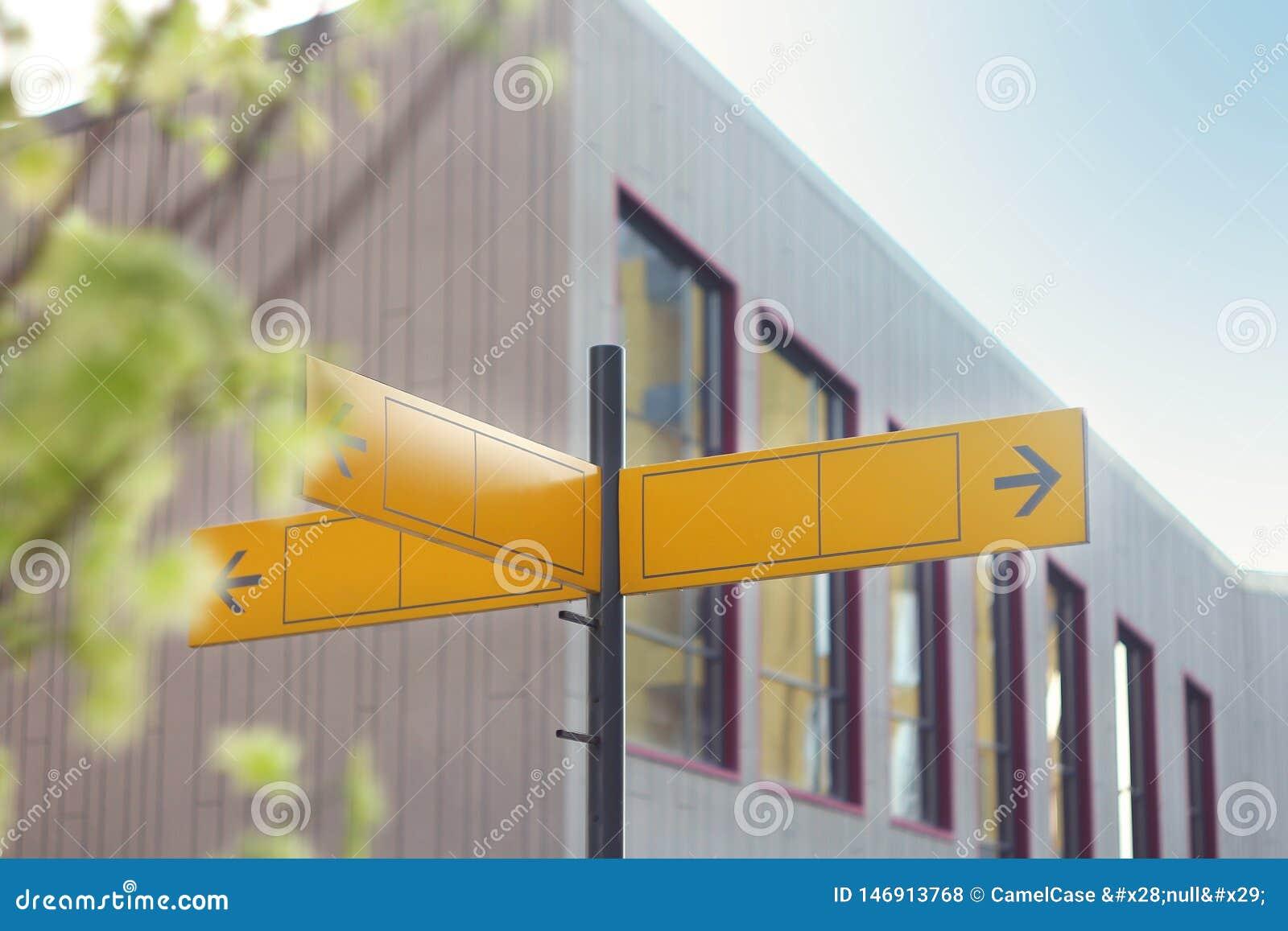 Panneau routier jaune ou panneaux routiers vides montrant la direction contre un bâtiment