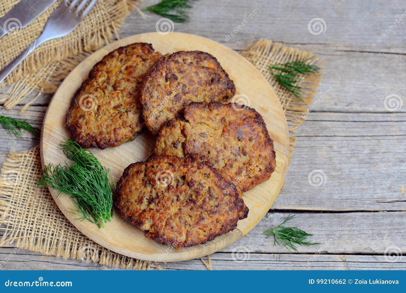 Pannkakor för feg lever med grönsaker på skärbräda- och tappningen träbakgrund med kopieringsutrymme för text