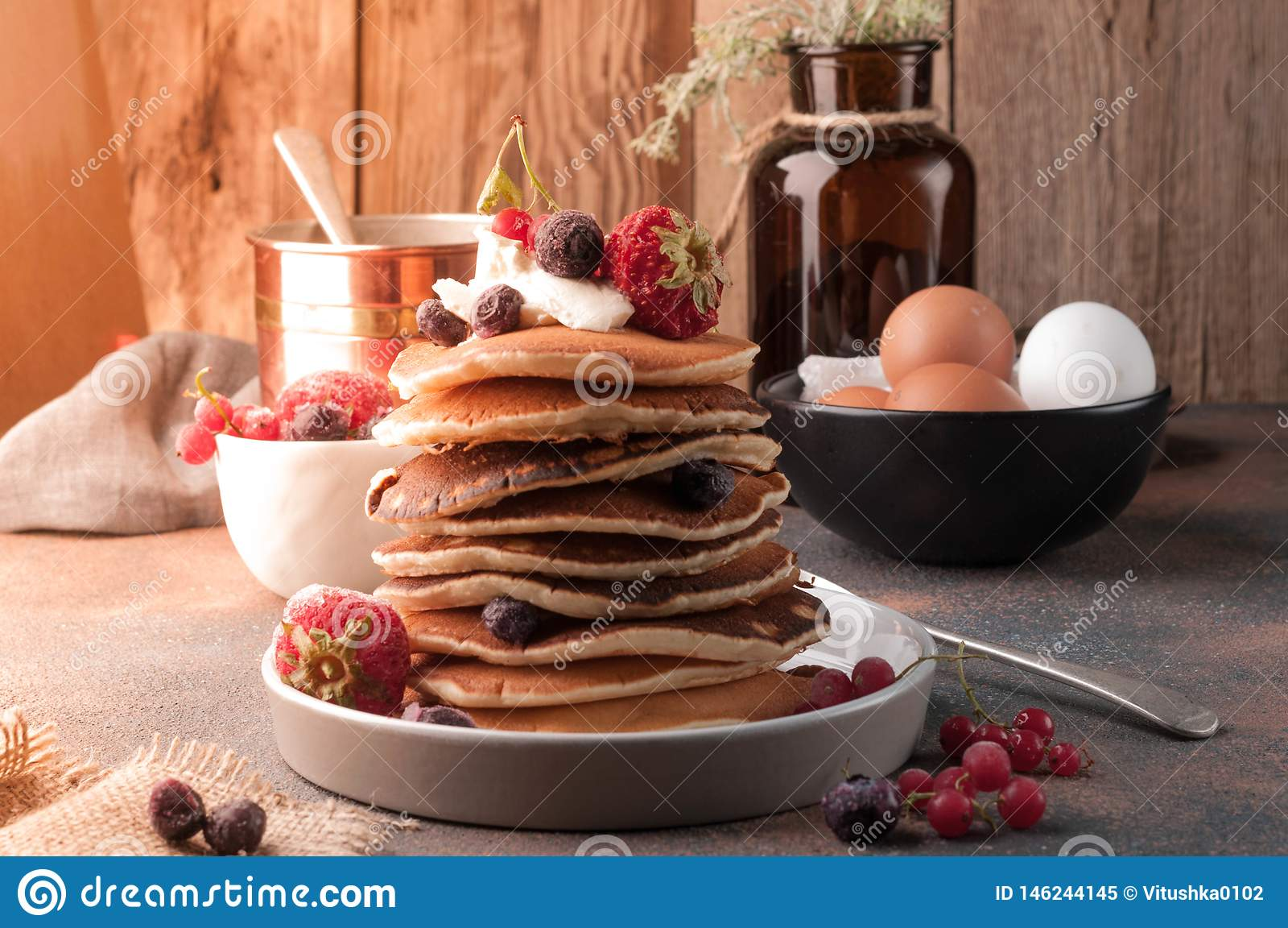 Pannkakor som staplas på den vita plattan med jordgubbar, blåbär och gräddfil