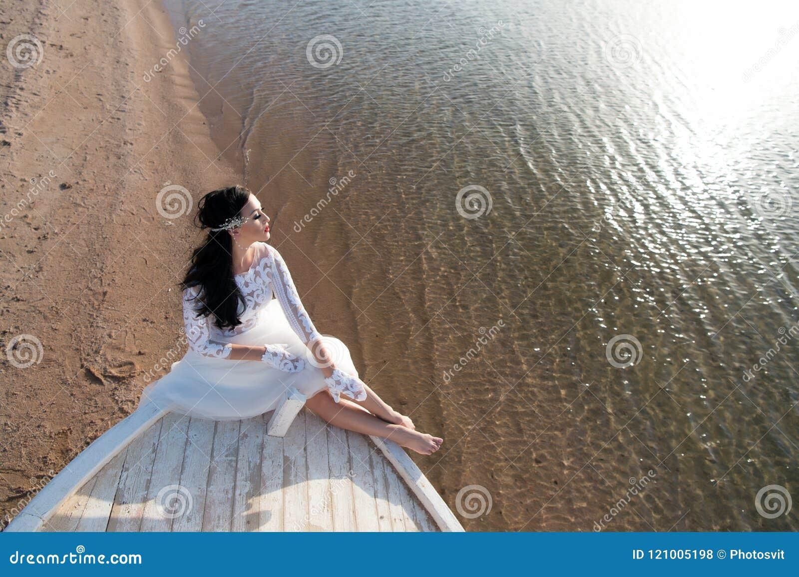 Panny młodej ślubnej sukni uroczy biały słoneczny dzień siedzi na łodzi lub statku Miesiąca miodowego morza plaża Rzeczy rozważaj