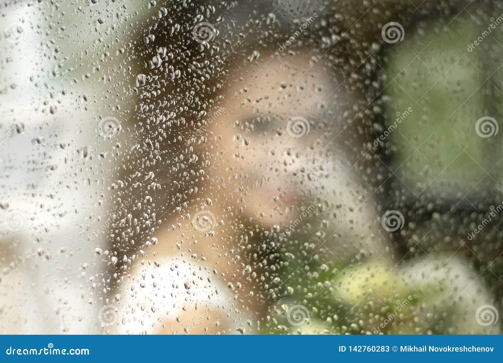Panny młodej sylwetka w ślubnej sukni z bukietem kwiaty przez szkła w podeszczowych kroplach
