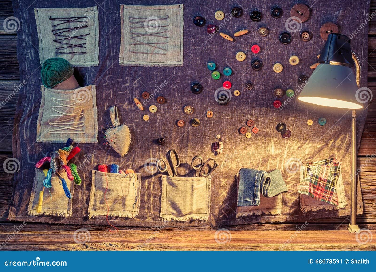 Pano da costura com tesouras, linhas e agulhas na oficina do alfaiate