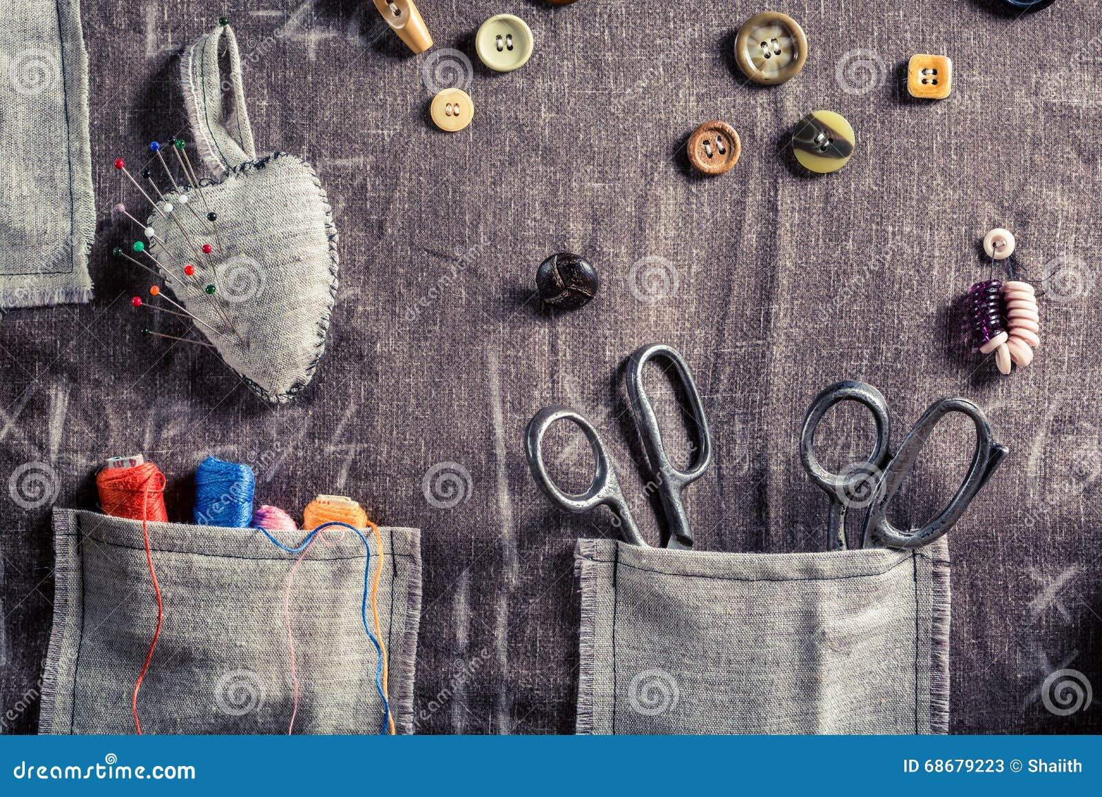 Pano feito a mão da costura com tesouras, linhas e agulhas na oficina do alfaiate