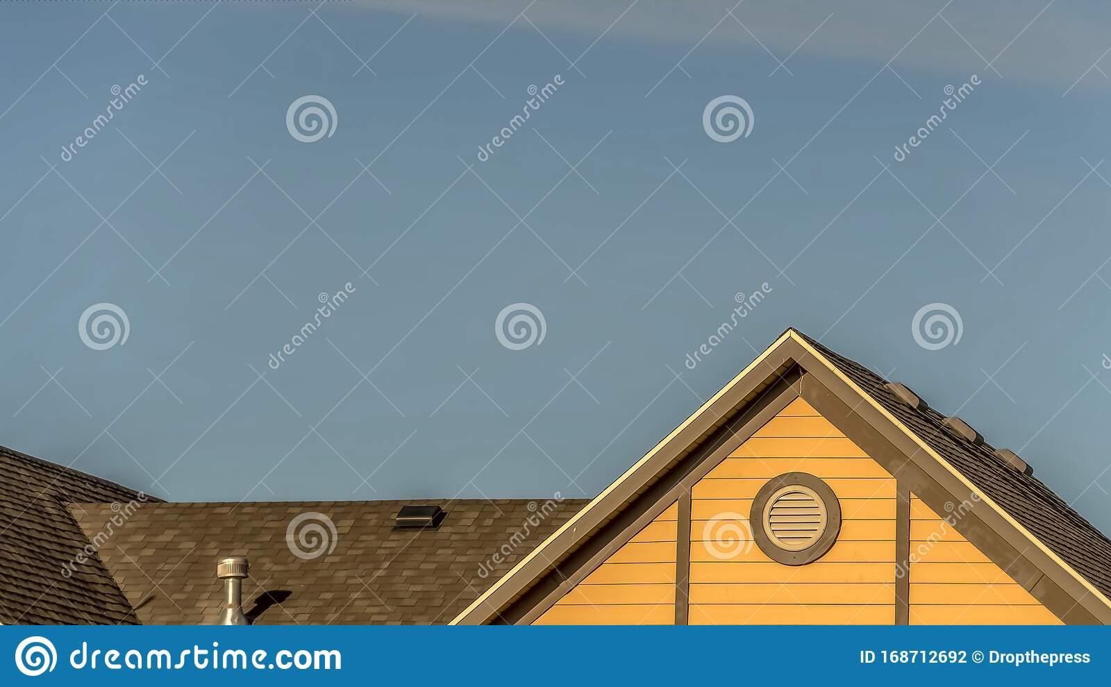 pano house exterior roof shingles round gable window against blue sky roofing construction chimney vent viewed sunny 168712692