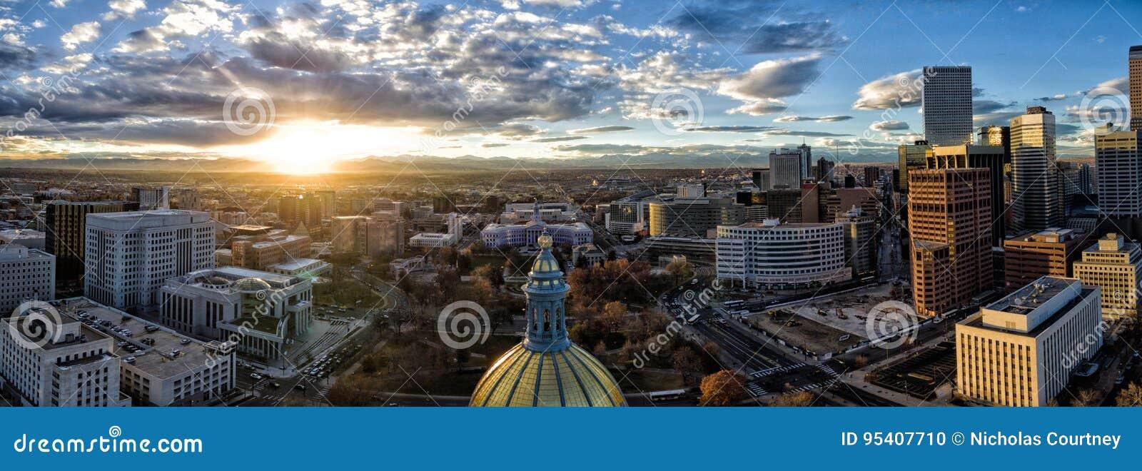Panorama aéreo del abejón - puesta del sol de oro imponente sobre el edificio y Rocky Mountains, Denver Colorado de la Capital de