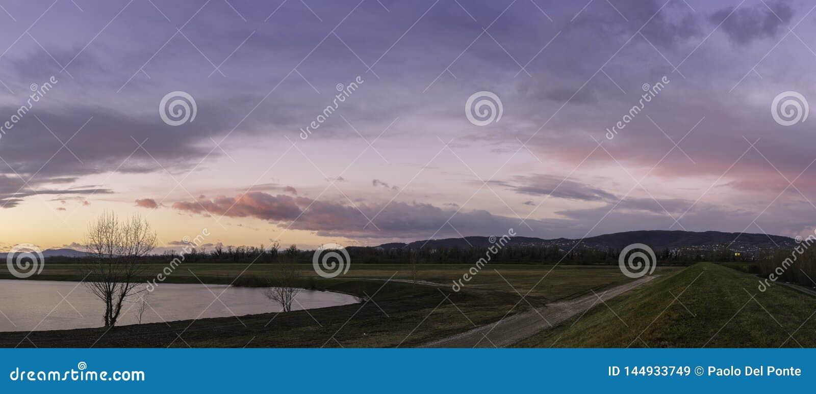 Panorama aan het westenkant van de stad van Zagreb met meer, bomen, weg op Sava-rivierdijk en bewolkte kleurrijke hemel in zonson