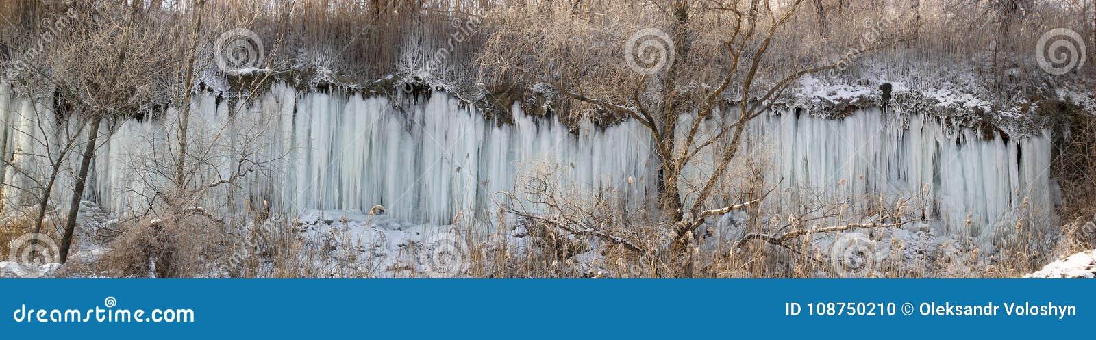 Panorama av lutningen av ravin, som streamlets av vatten körde och fryste längs i frosten som bildar en iskall vägg av beträffand