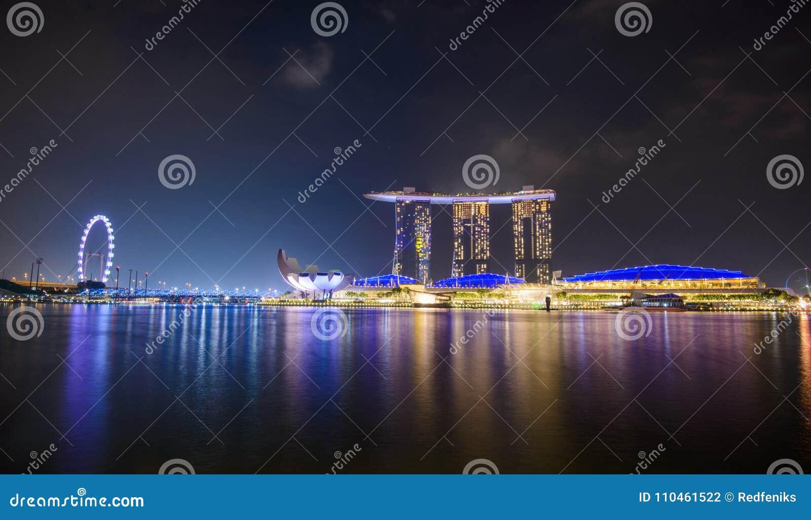 Panorama av Singapore stadshorisont med det Marina Bay Sands hotellet och det ArtScience museet på natten