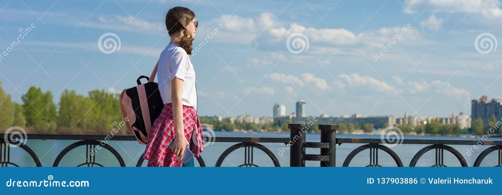 Panorama- baner av den kvinnliga studenten som går utomhus- Tonårig flicka i den vita t-skjortan med ryggsäcken, bakgrundshimmel