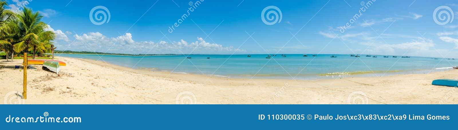 Panorama bonito da praia vermelha da coroa em Porto Seguro em Brasil em Baía, abandonado, com alguns barcos de pesca, uma árvore