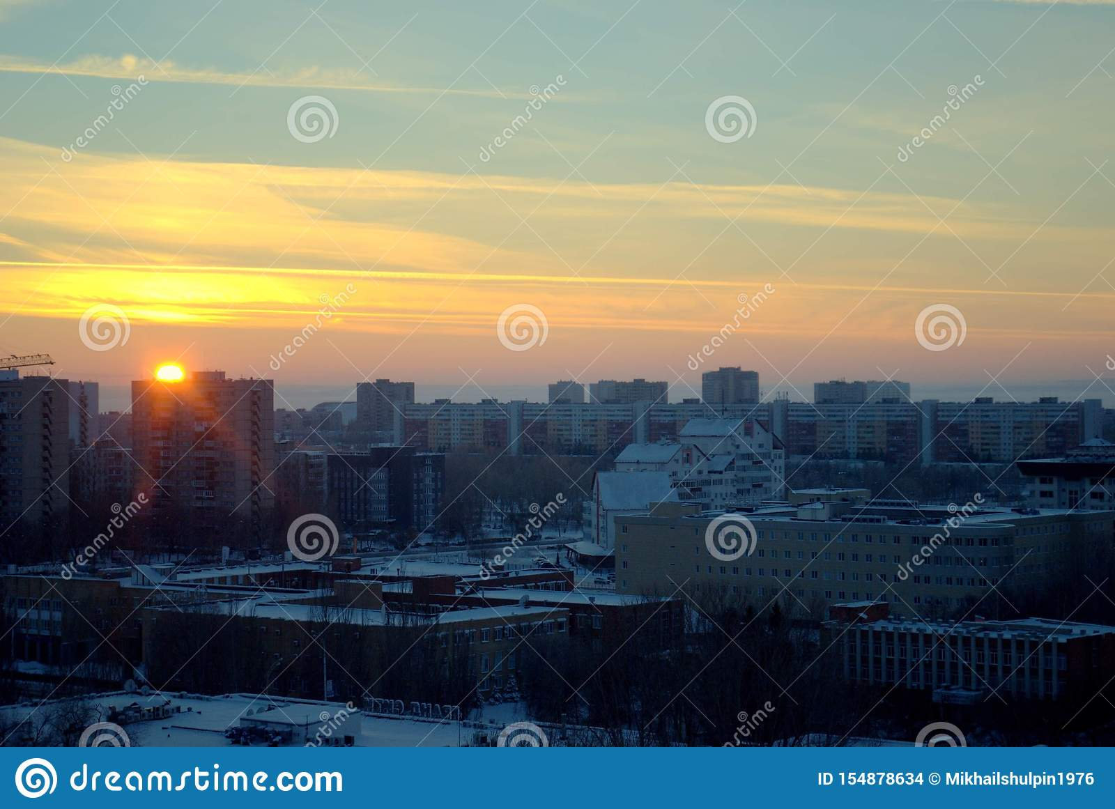 Panorama of the city on the background of a bright January sunset