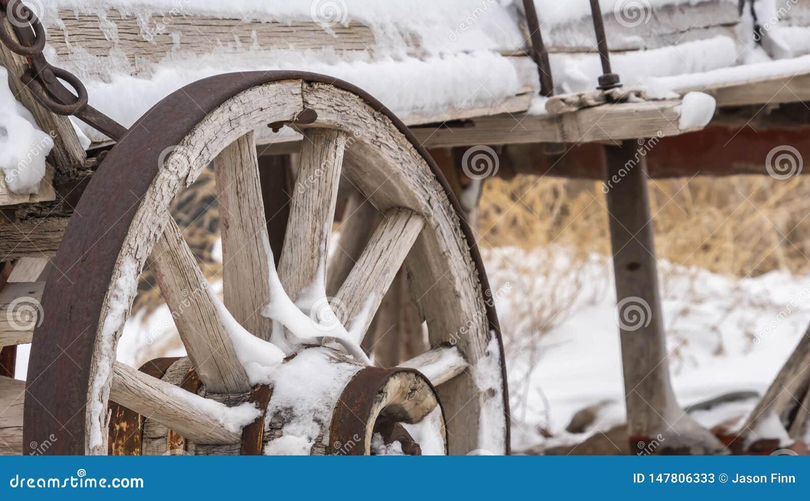Panorama claro um vagão de madeira velho com as rodas oxidadas espanadas com neve no inverno
