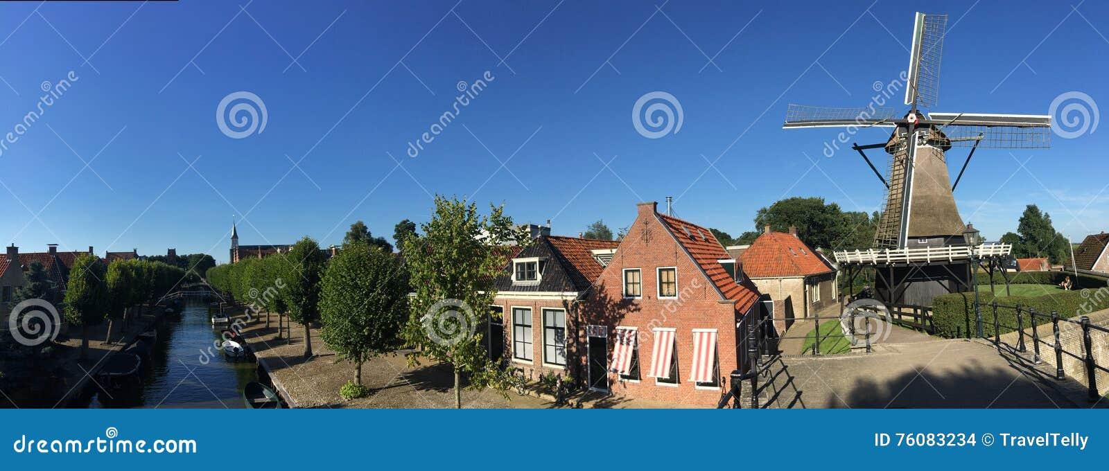 Panorama d un canal, des maisons et d un vieux moulin à vent
