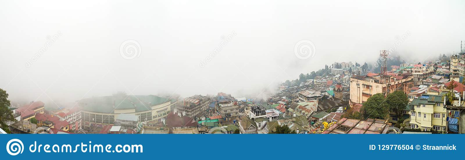 Panorama of Darjeeling city in East Bengal, India, and the surrounding mountains covered with thick fog
