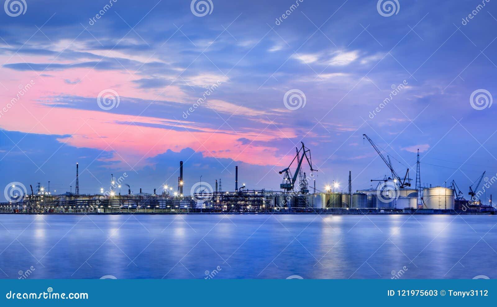 Panorama de una instalación de producción petroquímica contra un cielo coloreado dramático en el crepúsculo, puerto de Amberes, B