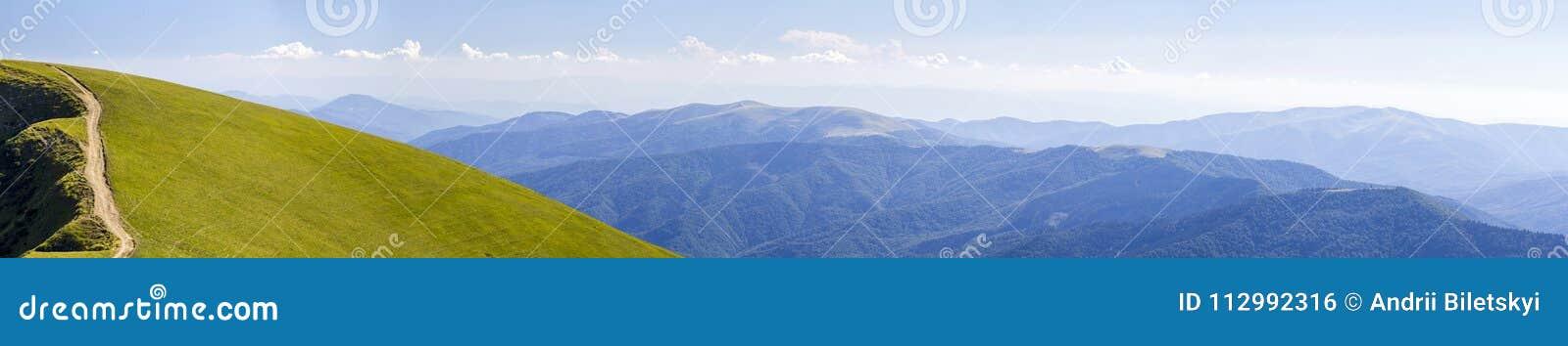 Panorama des collines vertes en montagnes d été avec la route de gravier pour