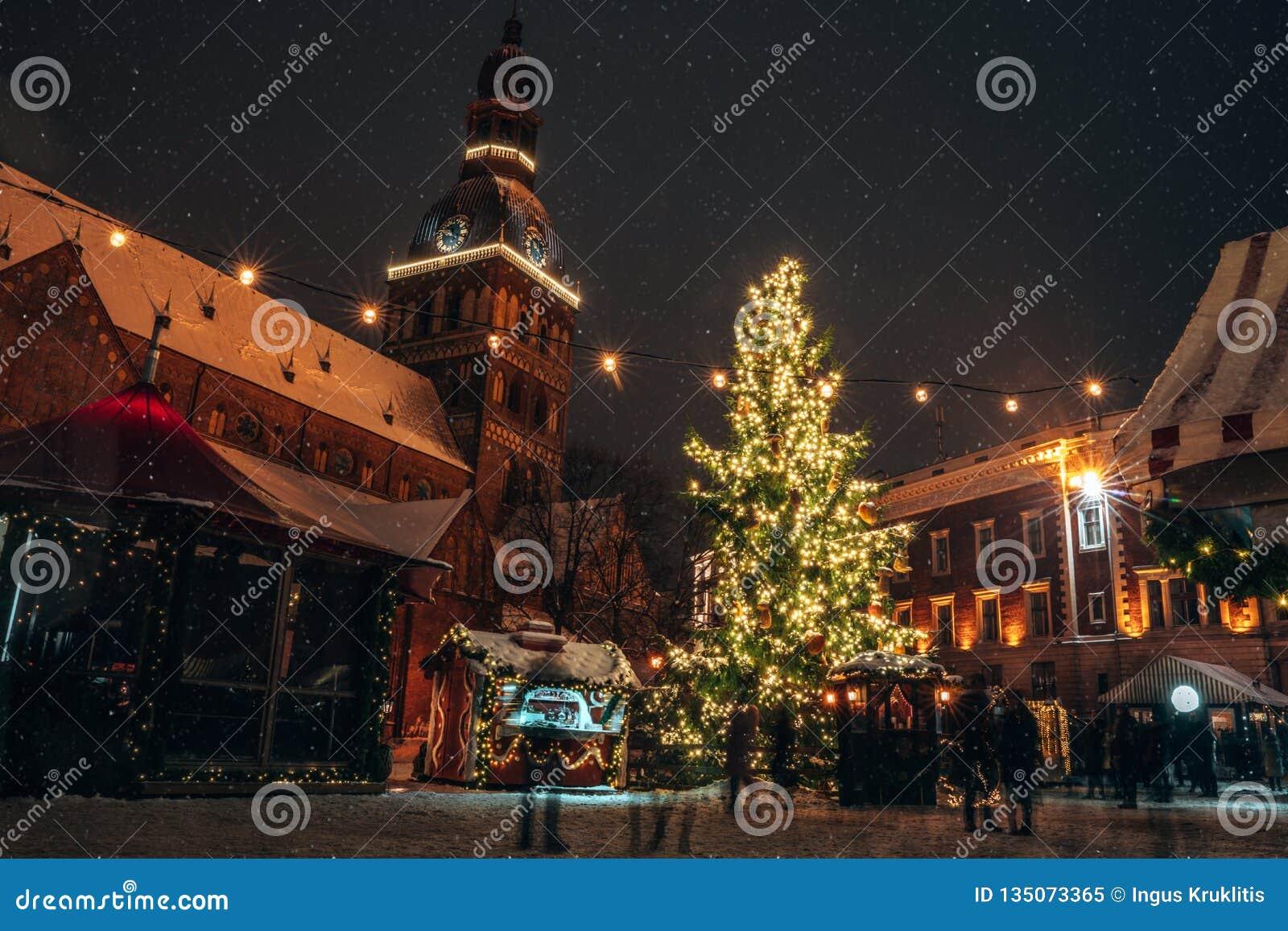 Panorama do mercado do Natal no quadrado da abóbada com a catedral da abóbada de Riga
