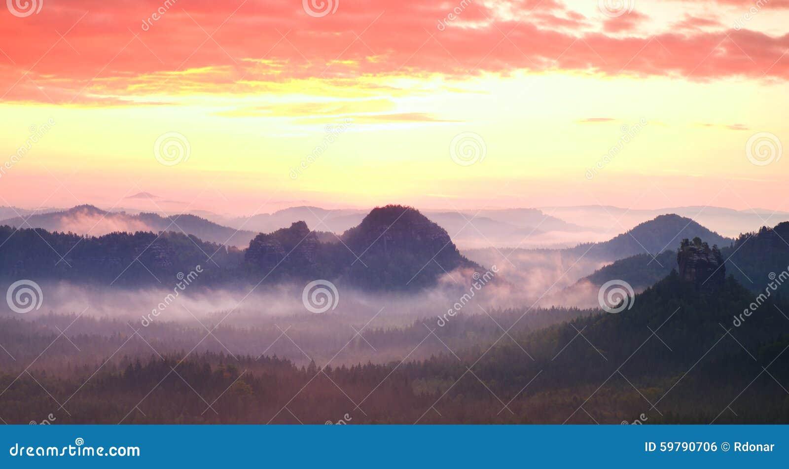 Panorama enevoado vermelho da paisagem nas montanhas Nascer do sol sonhador fantástico em montanhas rochosas Vale enevoado nevoen