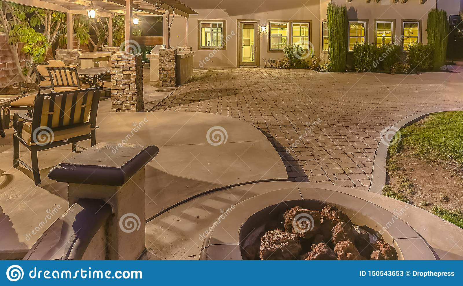 Panorama Frame Illuminated House With A Patio Accomodating An Outdoor Dining Area And Fire Pit Stock Image Image Of Pergola Grass 150543653