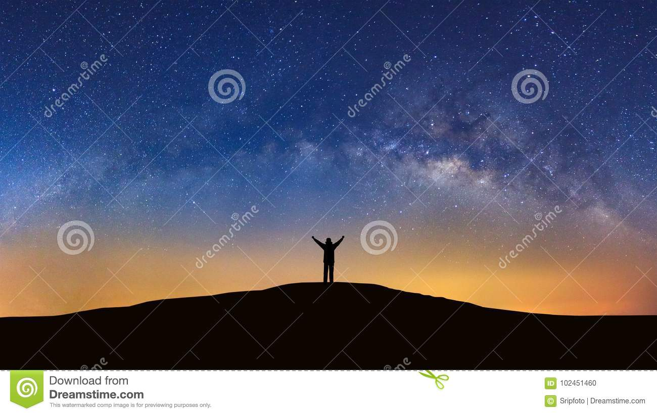 Panorama landscape with milky way, Night sky with stars and silhouette of a standing sporty man with raised up arms on high mount